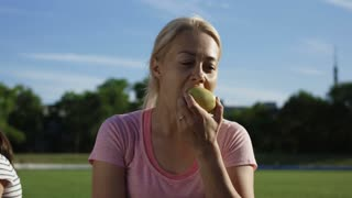 Sportive blond woman sitting on green athletic field in sunlight and enjoying apple