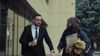 Successful businessman with coffee walking with the poor man on the street and talking with him