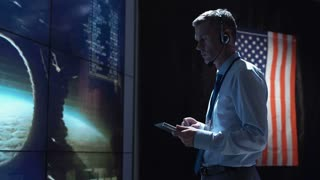 Supervisor man standing with tablet in space flight control center. Mars or Moon landing of spaceship. Elements of this image furnished by NASA