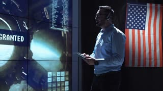 Supervisor man standing with tablet in space flight control center with American flag on background. Mars or Moon landing of spaceship. Then looking at camera. Elements of this image furnished by NASA