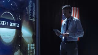 Supervisor man standing with tablet in space flight control center with American flag on background. Mars or Moon landing of spaceship