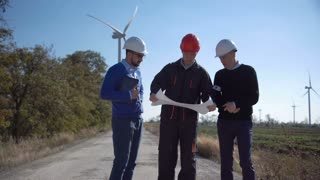 Team of three competitive coworkers collaborating on plan of building new sources of energy in field