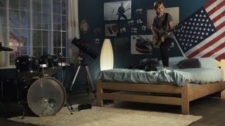 Teen boy in headphones jumping on bed in bedroom and playing guitar in dreams of being rock star in future