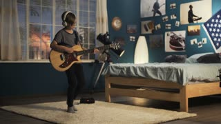 Teen boy in headphones moving on carpet in bedroom and playing guitar in dreams of being rock star in future