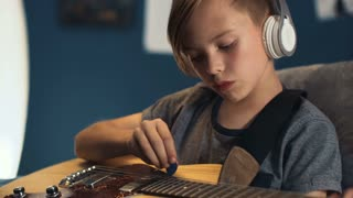 Teen boy sitting on bed at home and listening to music in headphones while practicing guitar