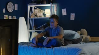 Teen boy sitting on cozy bed late at night and watching comedy on TV laughing with humorous jokes