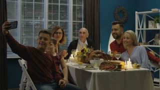 Teen boy sitting with parents and grandparents and sister at table on Thanksgiving day and taking selfie together using smartphone