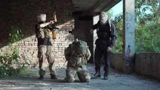 Terrorists torture the soldier having dressed a bag on the head and threatening with automatic machines