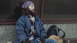 The bearded drunk homeless adult man sits on the street and swears on passersby