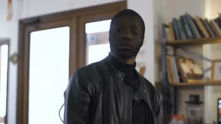 The blurred African robber aiming with the gun to the camera
