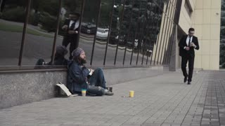The businessman banishes the bearded homeless man and throws back his cup with coins