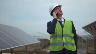 The businessman or architect on the solar panels mounting site talking the smartphone