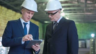 The businesspeople standing and talking in the warehouse. Holding digital tablet and showing something on screen. Horizontal indoors shot