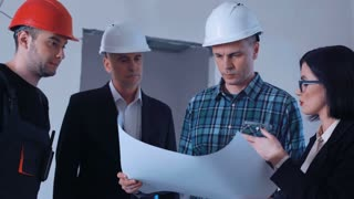 The group of architects engineers and workers in hard hat discusses blueprint