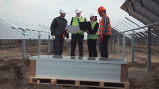 The group of engineers and workers in uniform on an incomplete field of photovoltaic panels discusses the plan of construction and mounting. They using blueprints and notebook