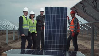 The group of people standing and holding a solar energy panel while looking at camera