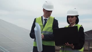 The men and woman engineers walking between rows of photovoltaic panels with blueprint between row of solar panels and checking blueprints using notebook and check quality of mounting