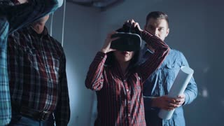 The people with blueprint and virtual reality headsets on a construction site. The woman shows to group of architects and engineers the project of future interior of the room in the 3D simulator