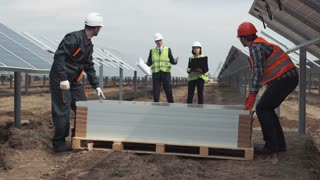 The supervisors with plan looking at builders mounting the solar energy panels. They holding notebook laptop and blueprints