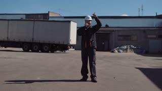 The warehouse worker talking to the radio set. Horizontal outdoors shot