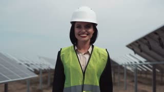 The woman engineer of power plant in a uniform and white hardhat, standing between rows of photovoltaic panels looks in the camera and smiles