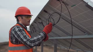 The worker in uniform and red hardhat talks on a radio and begins mounting of a photovoltaic panel on solar farm