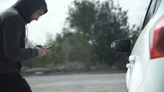Thief wearing hoodie hacking car using smartphone to open door and steal suitcase