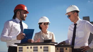 Three architects or engineers in hard hat having a meeting together working as a team as they stand discussing the model of a high-rise building project in their hardhats using a tablet computer