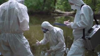 Three bio technicians testing for pollutants in a river in woodland wearing full hazard suits and masks as they take water samples