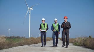 Three engineers in uniform wearing hard hat walking along road at wind farm on sunny day view front view
