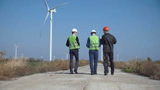 Three engineers wearing hard hats walking along road at wind farm on sunny day view from back