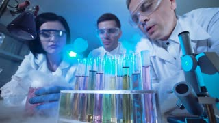 Three people in medical uniform looking at palette with test tubes in laboratory. Wide low angle