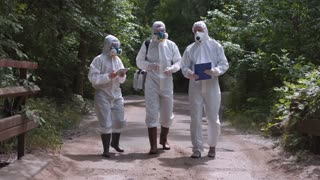 Three scientists wearing white protective suits standing on road in countryside discussing