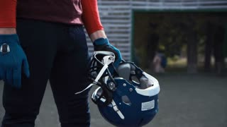 Tilt-up side view video shot of a determined bearded man putting his blue protective helmet before the beginning of an American football match