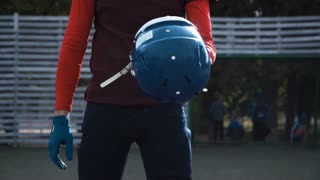 Tilt-up video shot of a determined bearded man putting his blue protective helmet before the beginning of an American football match