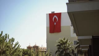 Turkish flag hanging on the wall of the house. National holiday and traditions of Turkey
