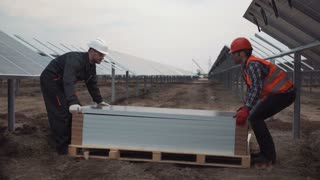 Two builders workers mounting the panels for the solar energy using