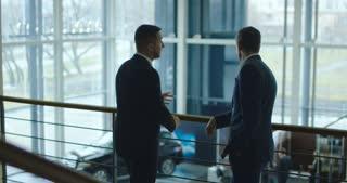 Two elegant men having conversation on balcony in car showroom. Slow motion