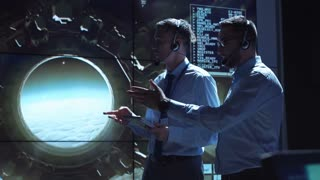 Two employees in headphones in the space flight control center discuss the flight of a spacecraft and make a video contact with a satellite in space