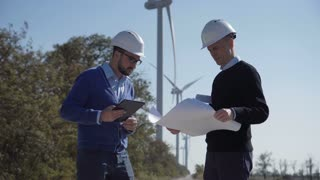 Two engineers discussing a blueprint on a wind farm in front of a turbine supplying alternative electricity from the conversion of kinetic energy