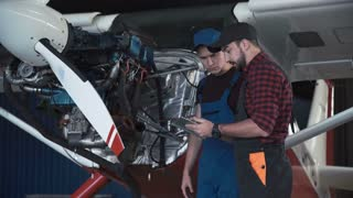 Two flight mechanics doing a pre flight check or maintenance on a small single engine aircraft in a hangar in a close up view of them working on the engine