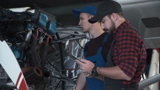 Two flight mechanics doing a pre flight check or maintenance on a small single engine aircraft using digital tablet in a hangar in a close up view of them working on the engine