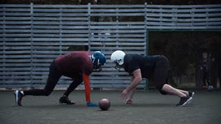 Two helmeted football players in two different uniforms pushing past each other with fence in background