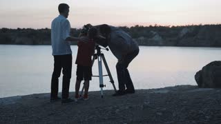 Two men and boy using telescope watching stars on shore of lake in twilight