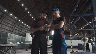 Two men discussing over digital tablet in aircraft hangar