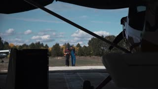 Two men entering hangar, looking at plane and talking with each other