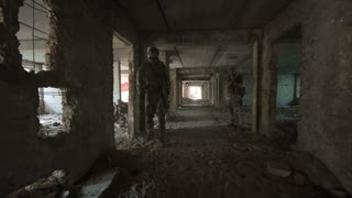 Two men in special clothing holding guns and walking slowly inside of ruined building