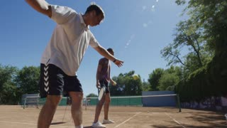Two men in sportswear standing on tennis court and playing game against wall hitting balls with rackets in sunlight