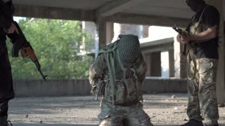 Two men in uniform attacking terrorists and freeing hostage inside of ruined building