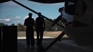 Two men standing in hangar and talking with each other